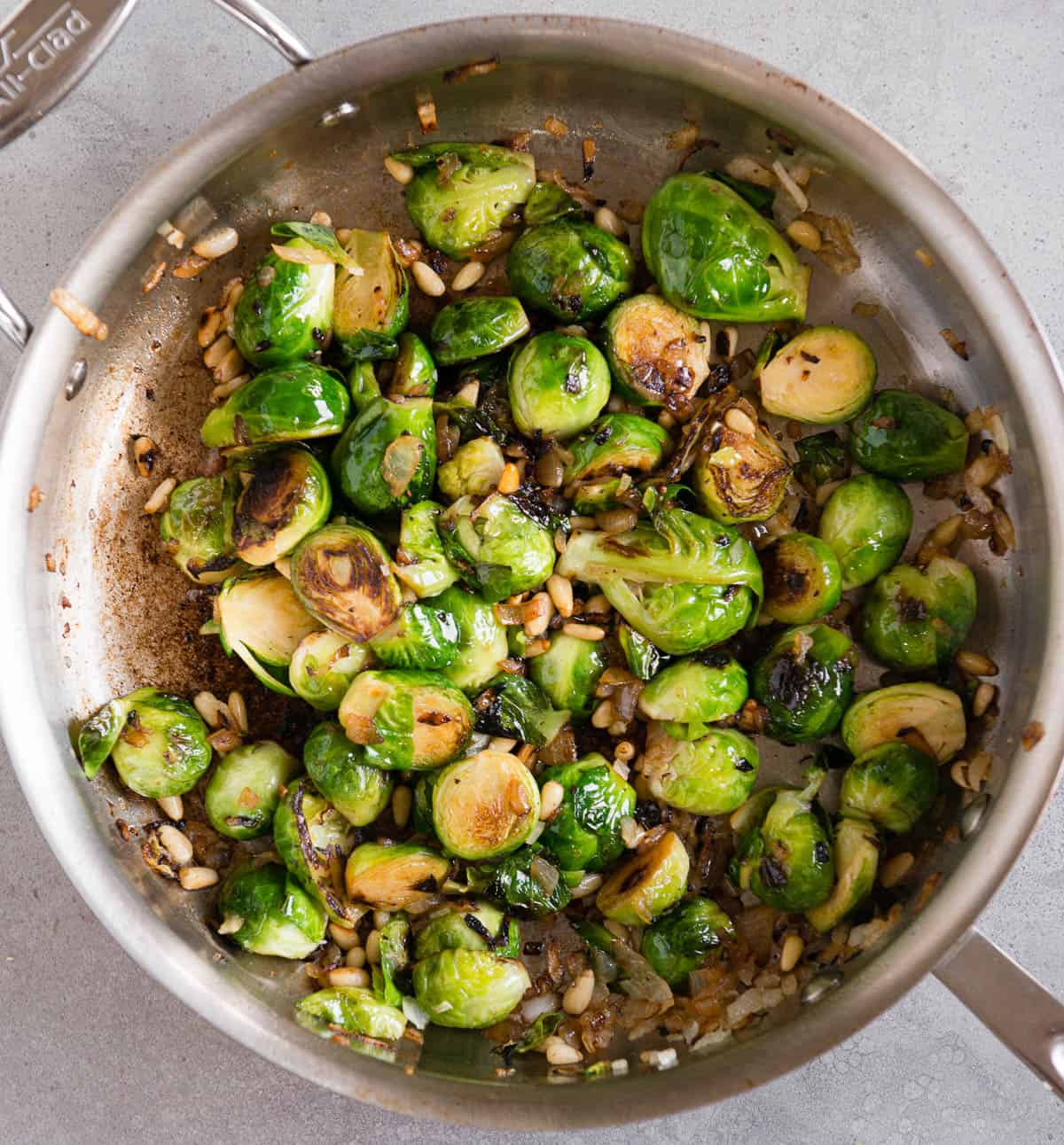 browned Brussels Sprouts with onion and pine nuts in pan