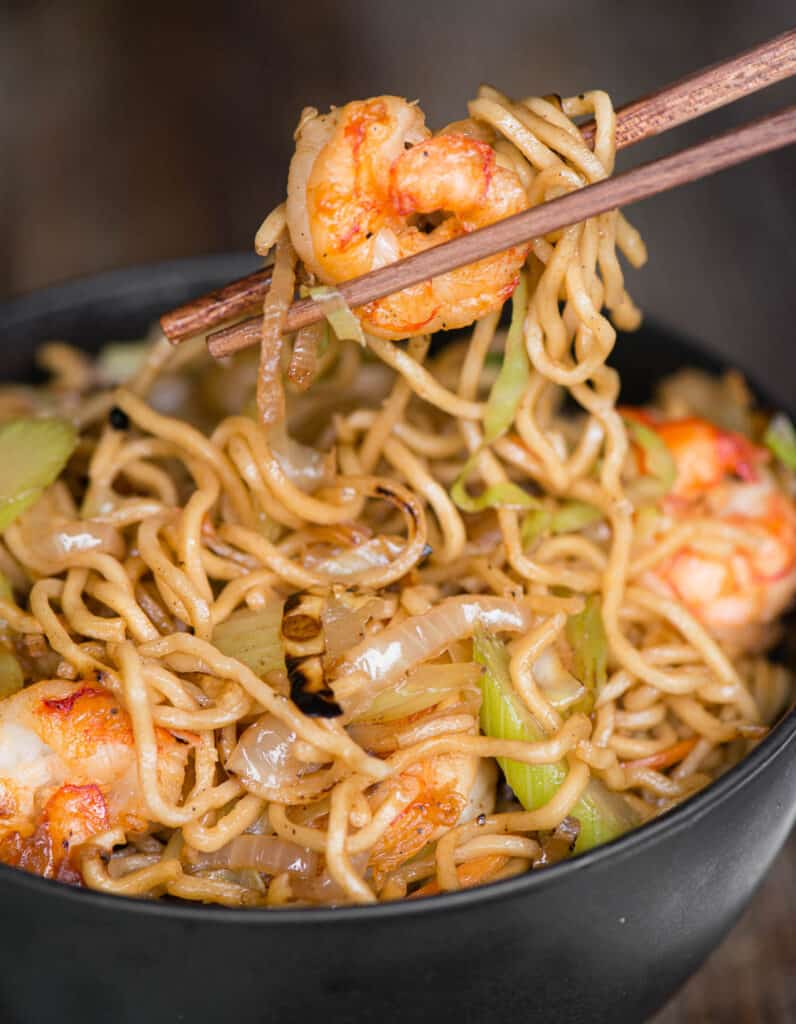 chopsticks lifting bite of shrimp with chow mein noodles