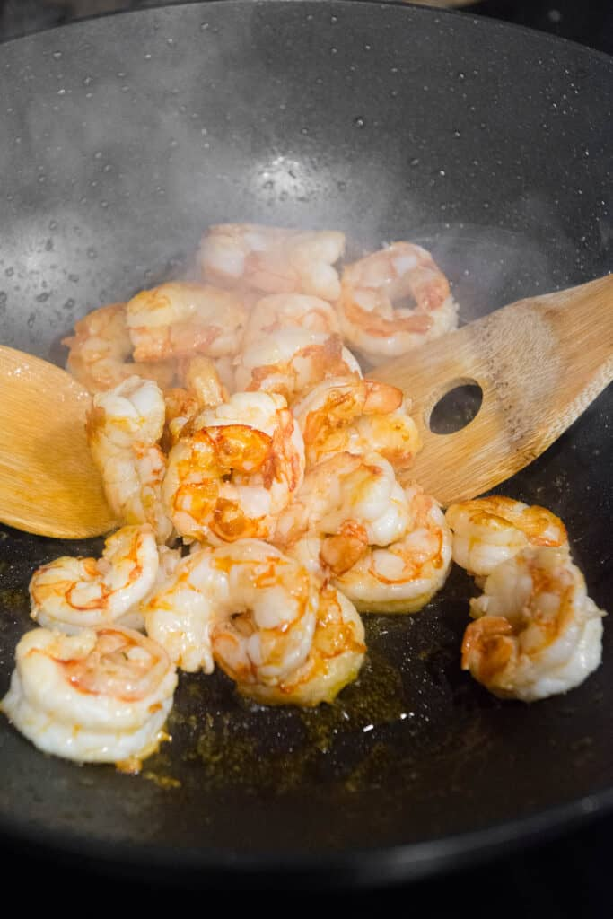 cooking shrimp in wok with wooden spoons