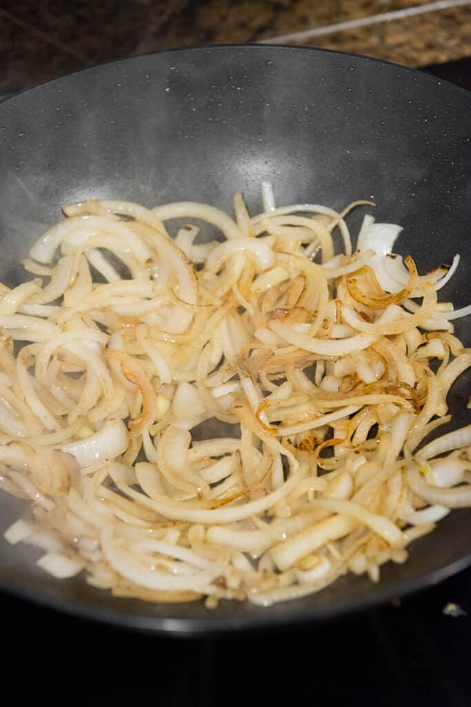 browning onion slices in wok pan
