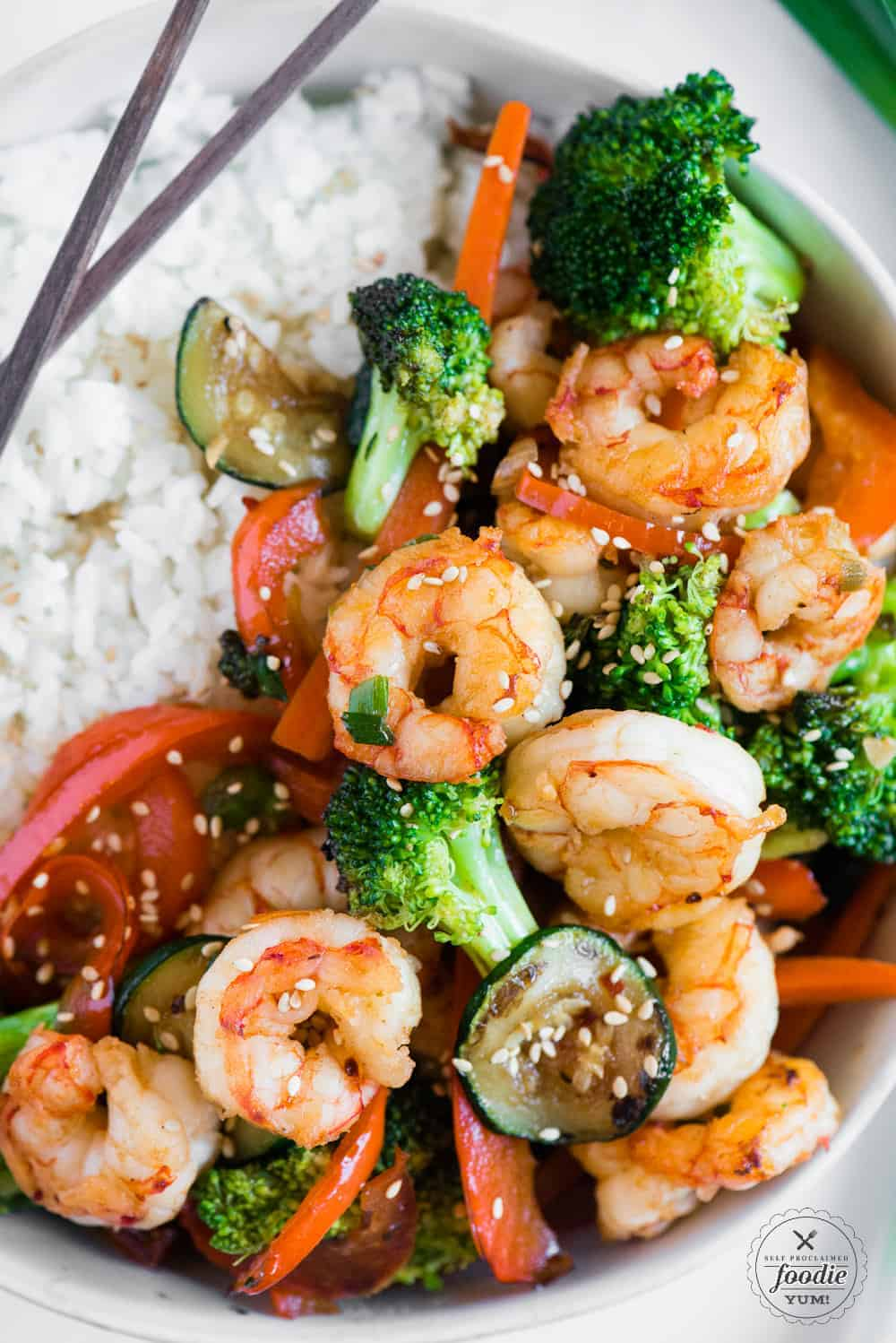healthy bowl of shrimp stir fry with sauce and rice