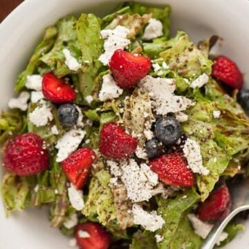 A bowl of salad with goat cheese and berries