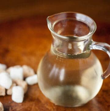 simple syrup in small glass pitcher with sugar cubes