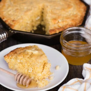 slice of cornbread on plate with honey