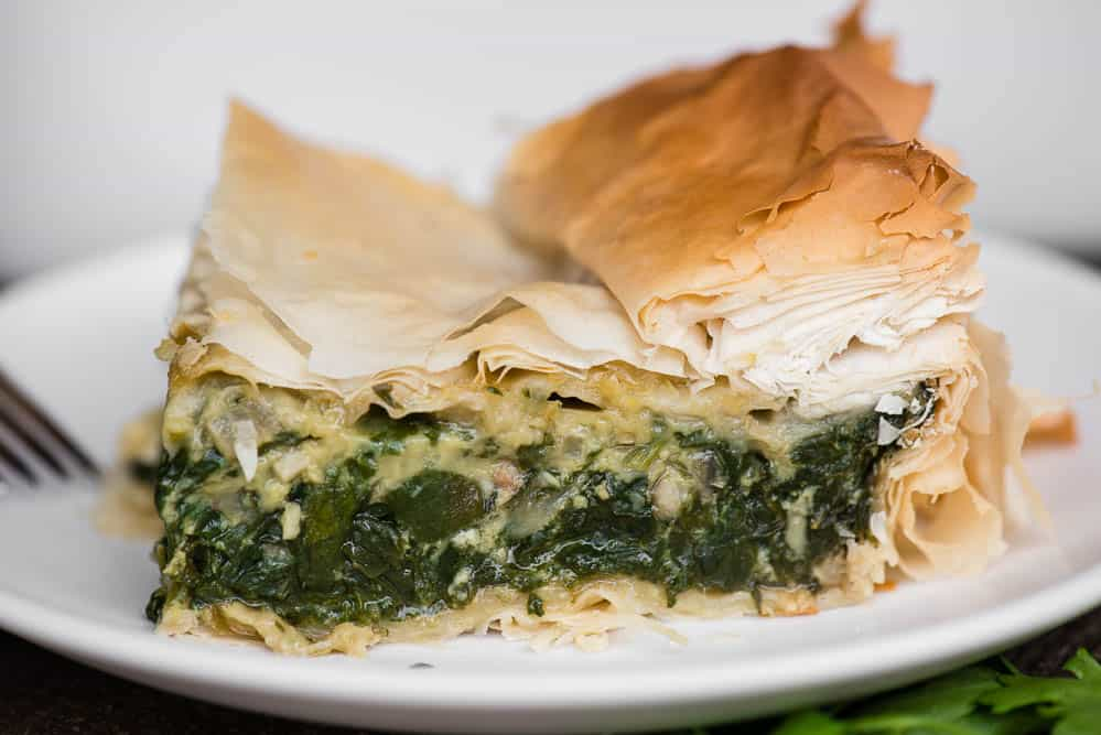 slice of homemade spanakopita with fresh spinach