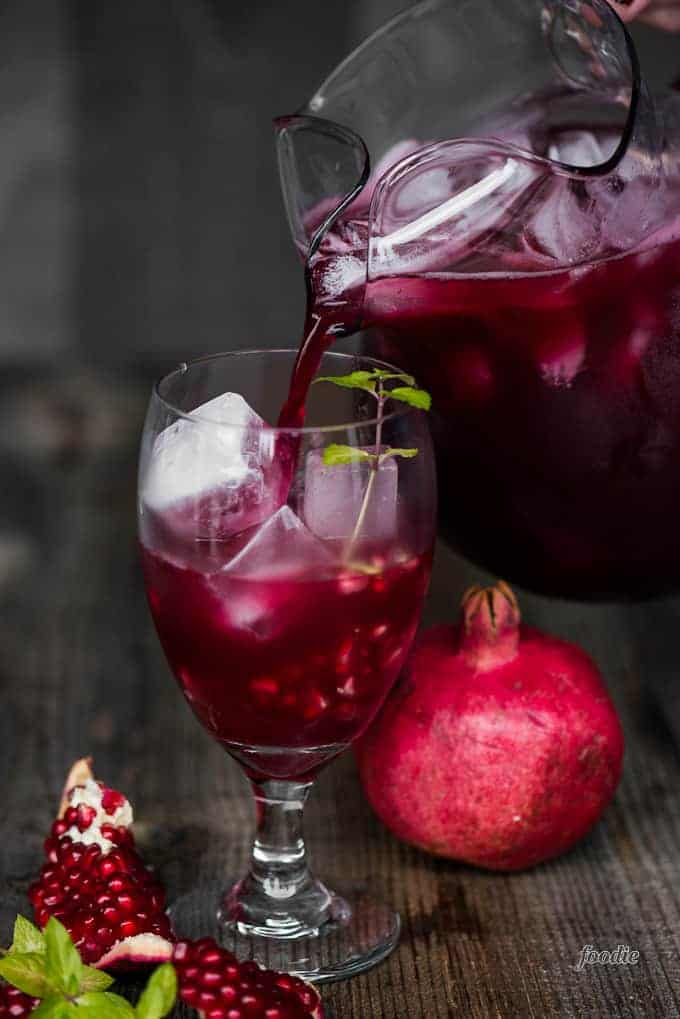 pitcher of pomegranate cocktail pouring into glass