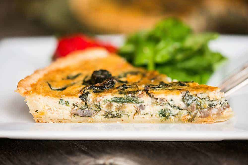 slice of spinach quiche with mushrooms.
