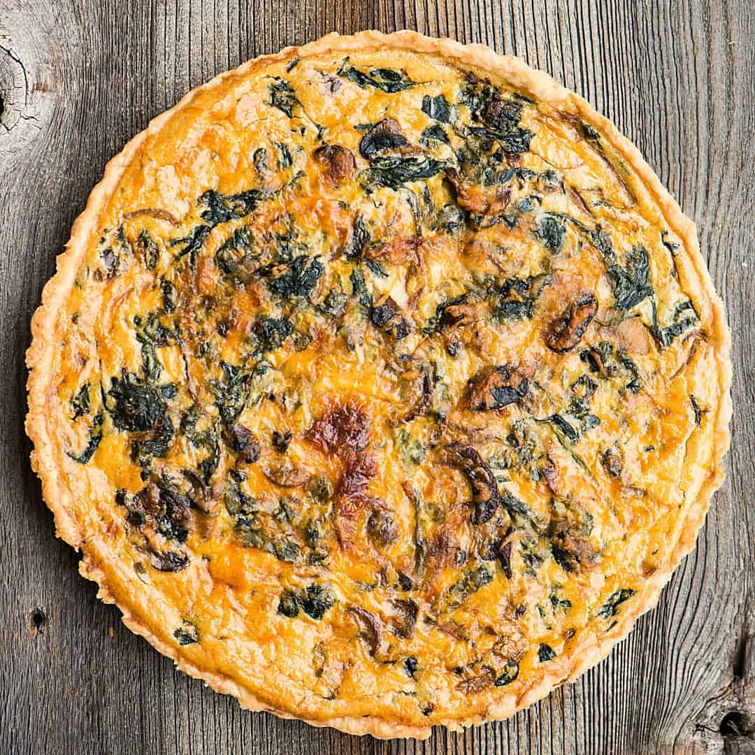 top of a whole quiche with spinach and mushrooms