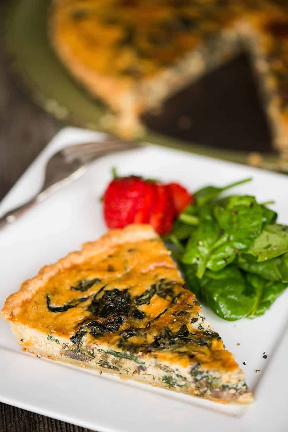 slice of homemade quiche on plate with spinach