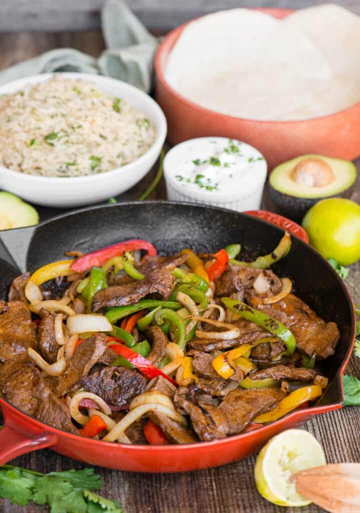 homemade Steak Fajitas in skillet with toppings