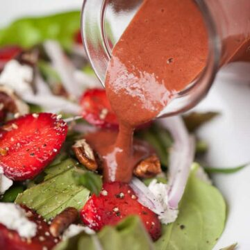 strawberry basil vinaigrette being poured on a salad