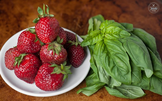 a plate of strawberries and basil