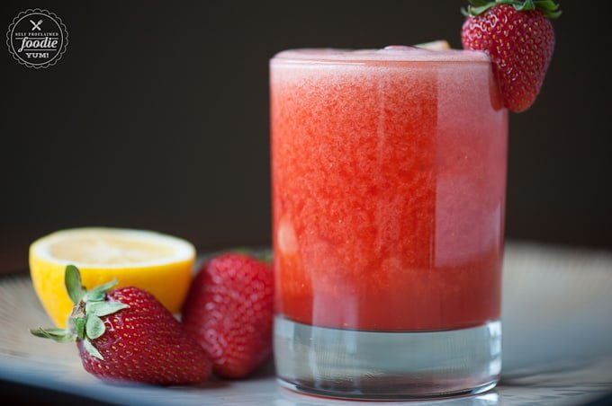 A close up of a glass of whiskey with Strawberry and Lemonade
