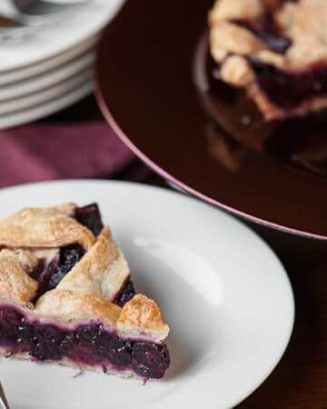 A piece of homemade berry pie on a white plate
