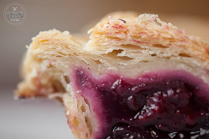 A close up of flaky pie crust with berry filling