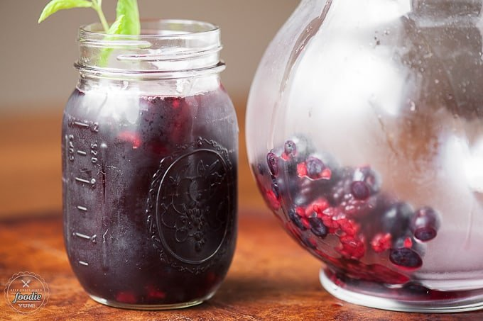 mason jar full of Sangria next to pitcher with berries