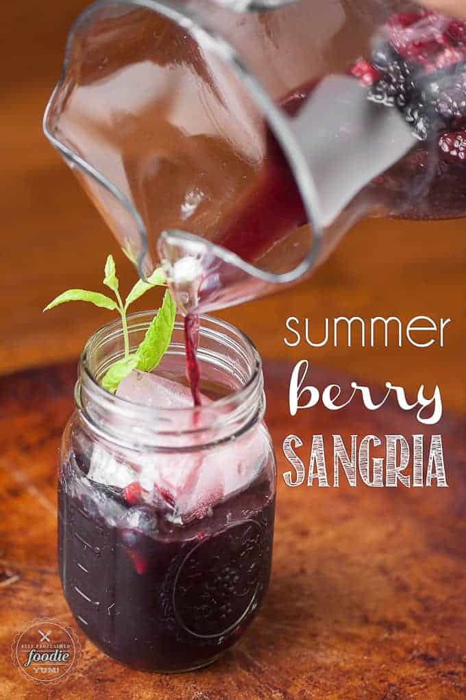 Pouring berry sangria from a pitcher to a mason jar