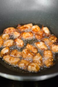 diced chicken breast frying in oil