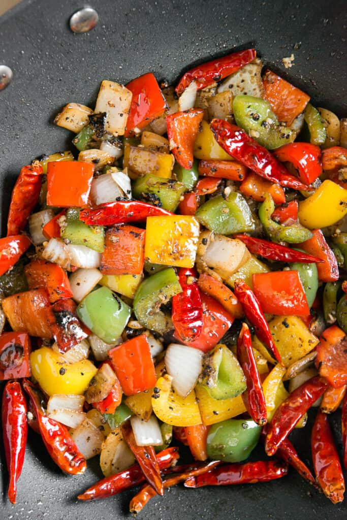 sauteed peppers and onions in wok pan