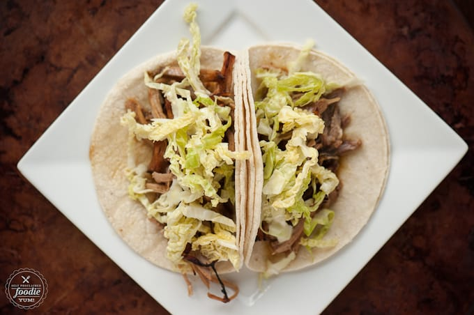 corn tortillas, meat, and lettuce on a plate