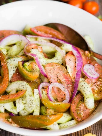 bowl of marinated tomato cucumber salad with heirloom tomatoes