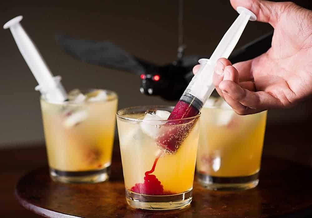 Vampire Cocktail is the perfect spooky Halloween drink. Syringes filled with sweetened raspberry puree look gory, but taste amazing!