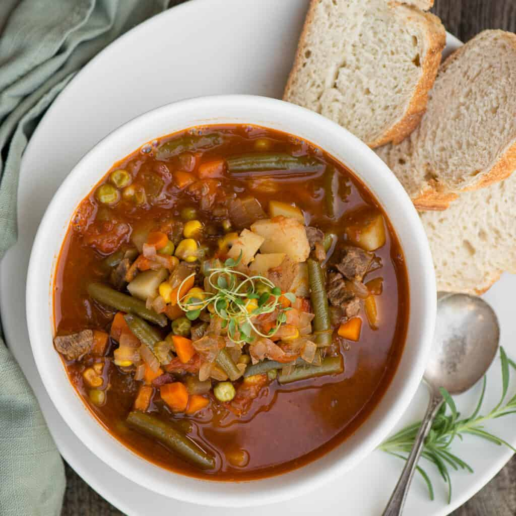 looking down at beef and vegetable soup in bowl with bread