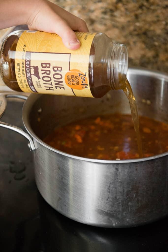 adding broth to soup on stove