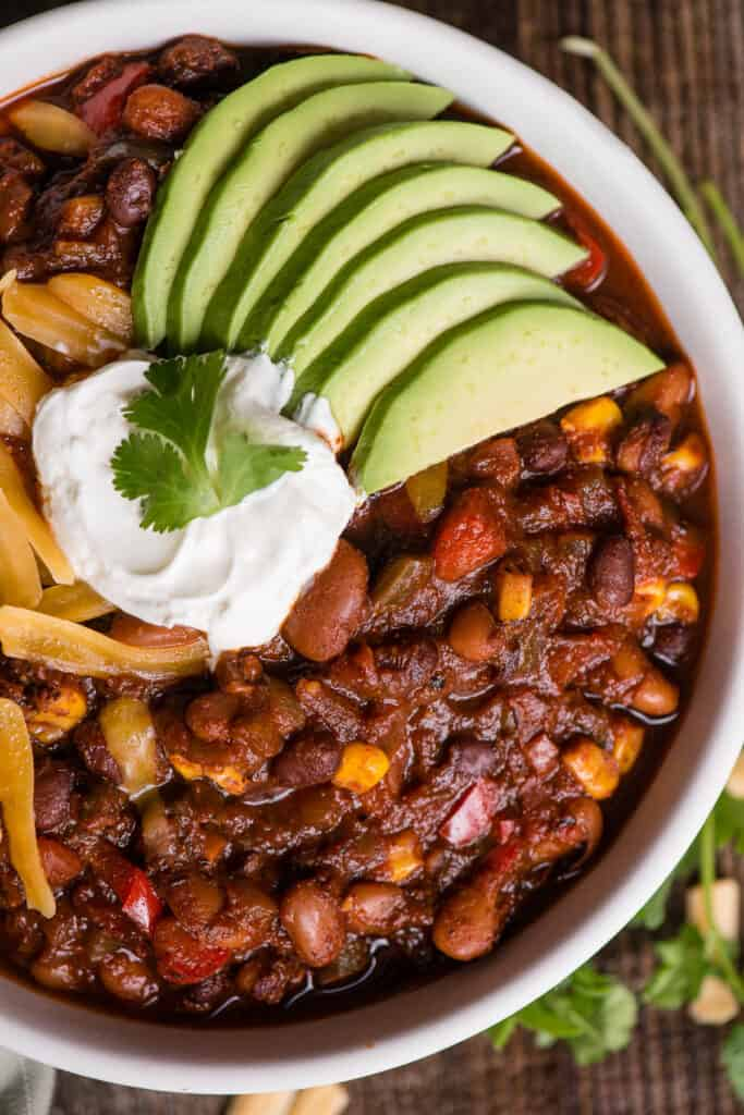 close up of a bowl of homemade vegetarian chili with toppings