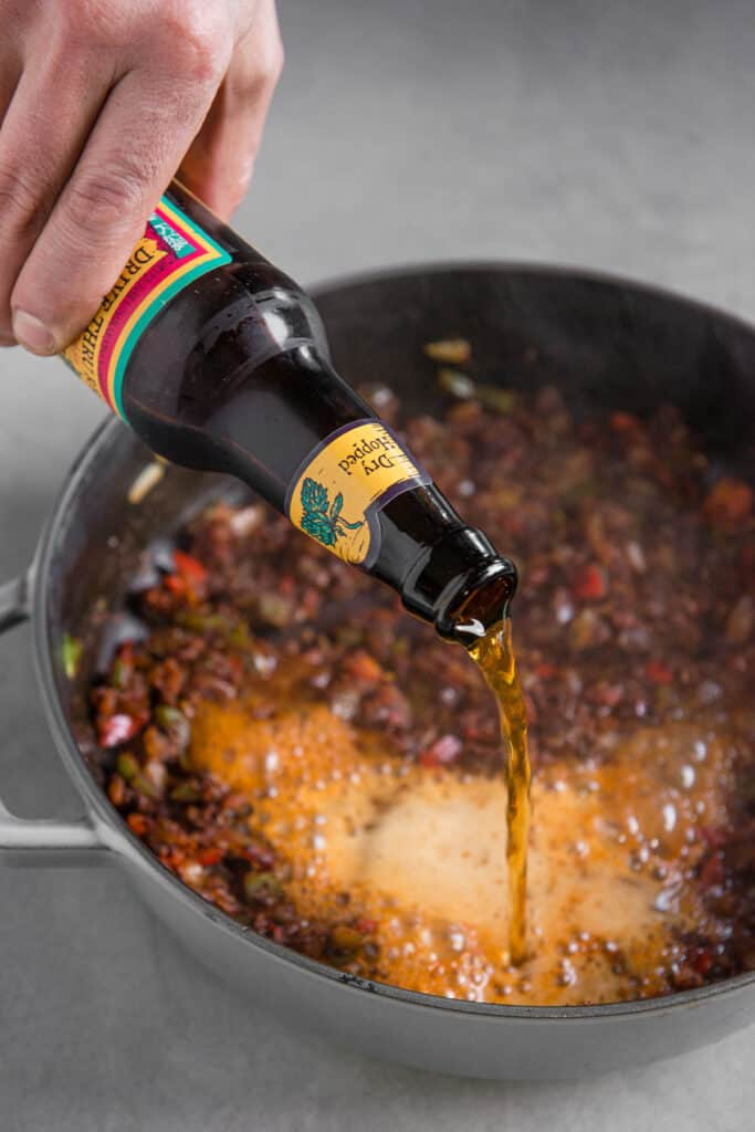 pouring beer into vegetarian chili recipe