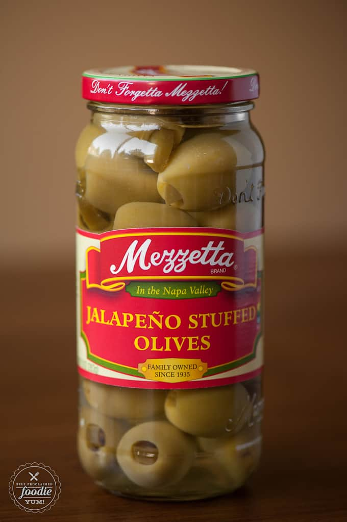 Impress your guests with this easy to make yet insanely delicious two-bite spicy Warm Cheddar Jalapeno Olives appetizer.