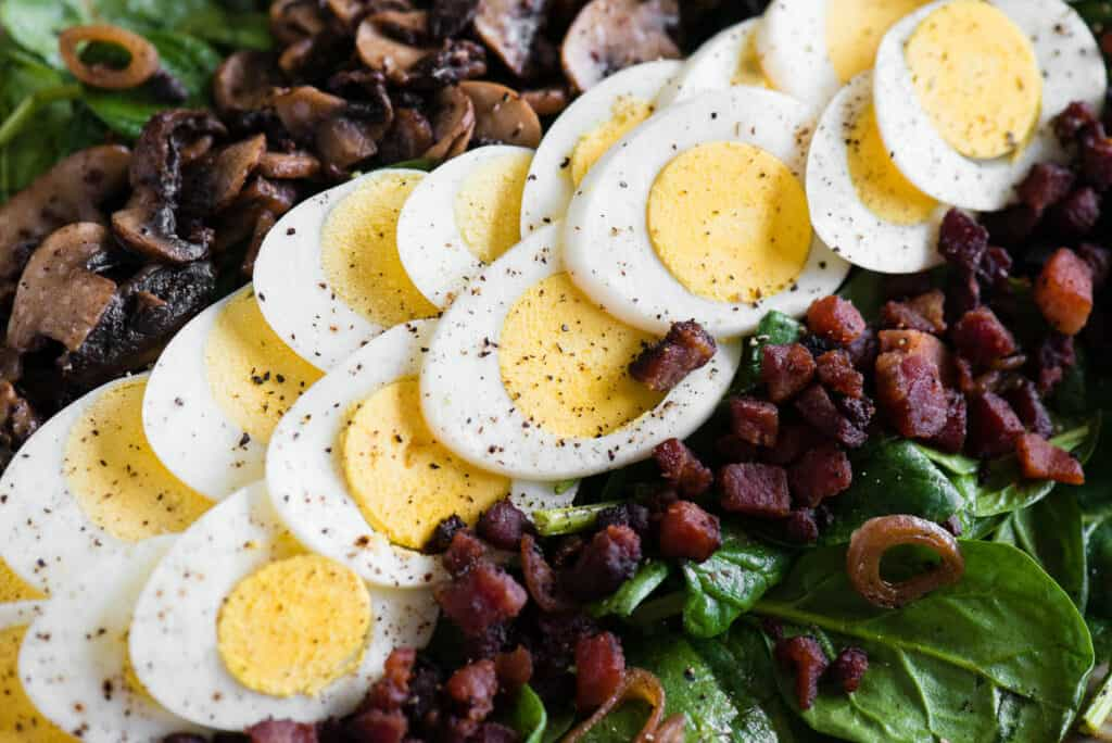 slices of hard boiled egg with cooked bacon on spinach salad