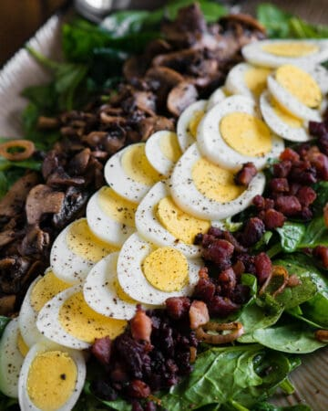 hard boiled egg on top of bacon spinach salad
