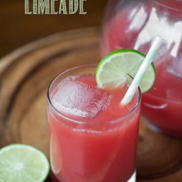 watermelon limeade in glass next to pitcher